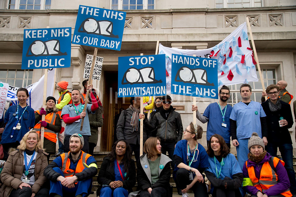 Hackney London February 10th 2016. Second one day strike by junior doctors  protesting against proposed changes to their contract including payment for working on Saturdays. Picket at Hackney Town Hall with placards by artist Stik, an image of a baby orignally made for Homerton Hospital. Stik stands in the centre wearing sunglasses.