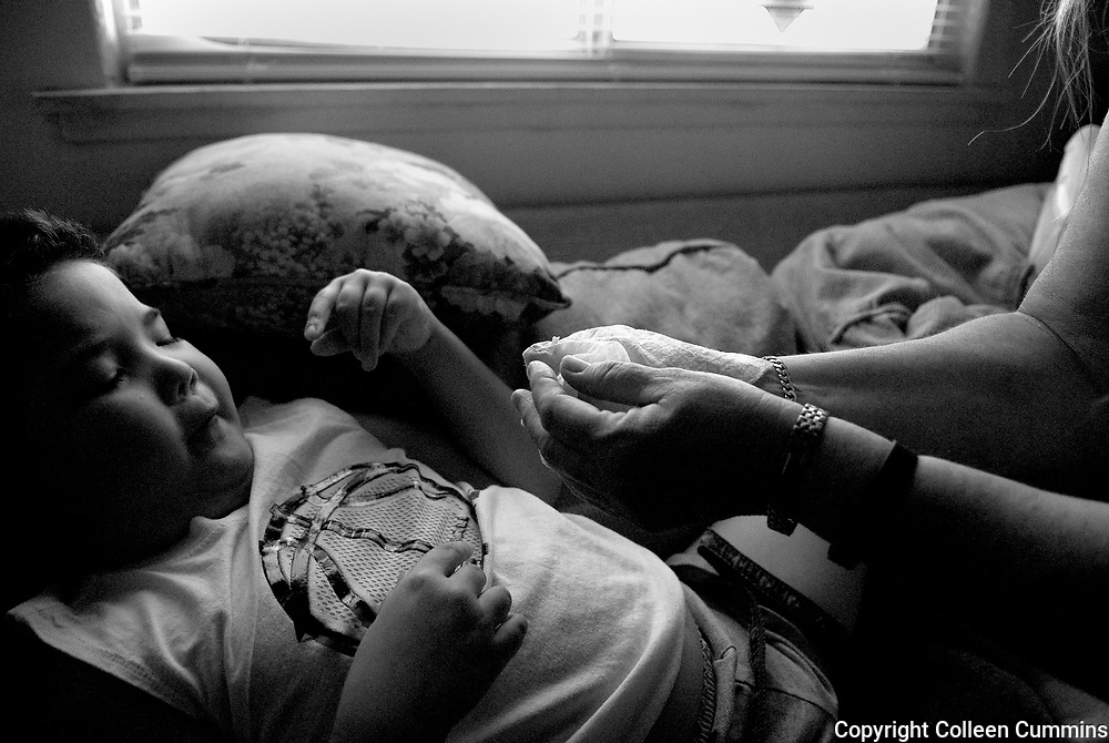 Since Alex has been nonverbal his whole life Mary relies on instinctive knowledge she has gained over time while caring for her grandson. Alex had climbed up on to the couch lit and began to started gesturing towards his mouth as he lay on his back. Mary explained that Alex was in the process of losing his baby teeth. Mary then gently reached into Alex's mouth and helped wiggle free a small front tooth.