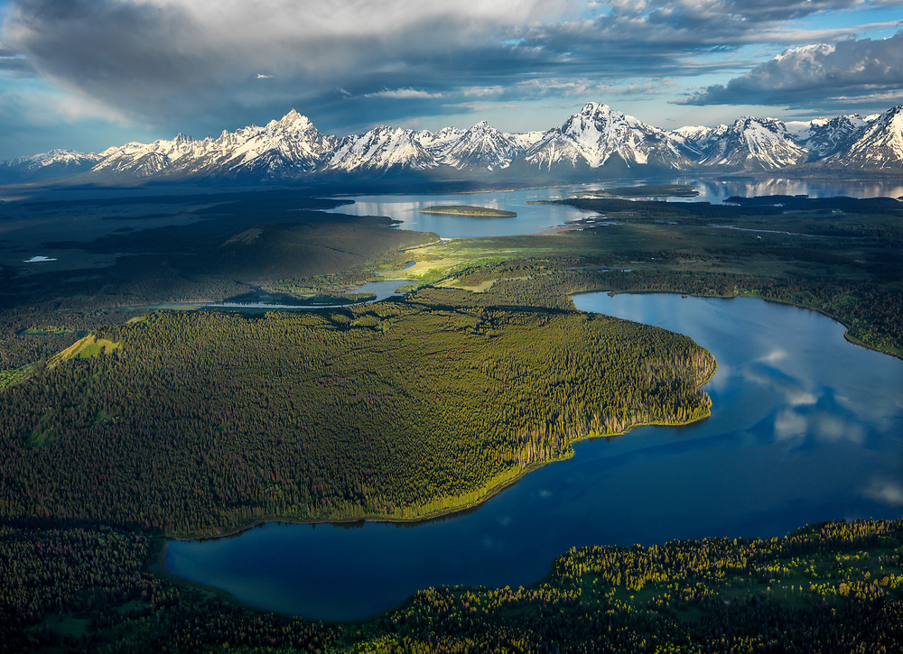 Aerial view of the South Fork of the Snake River in which creates Jackson Lake in distance at base of the Tetons and Emma Matilda Lake in foreground in Teton National Park in early summer near Jackson, Wyoming
