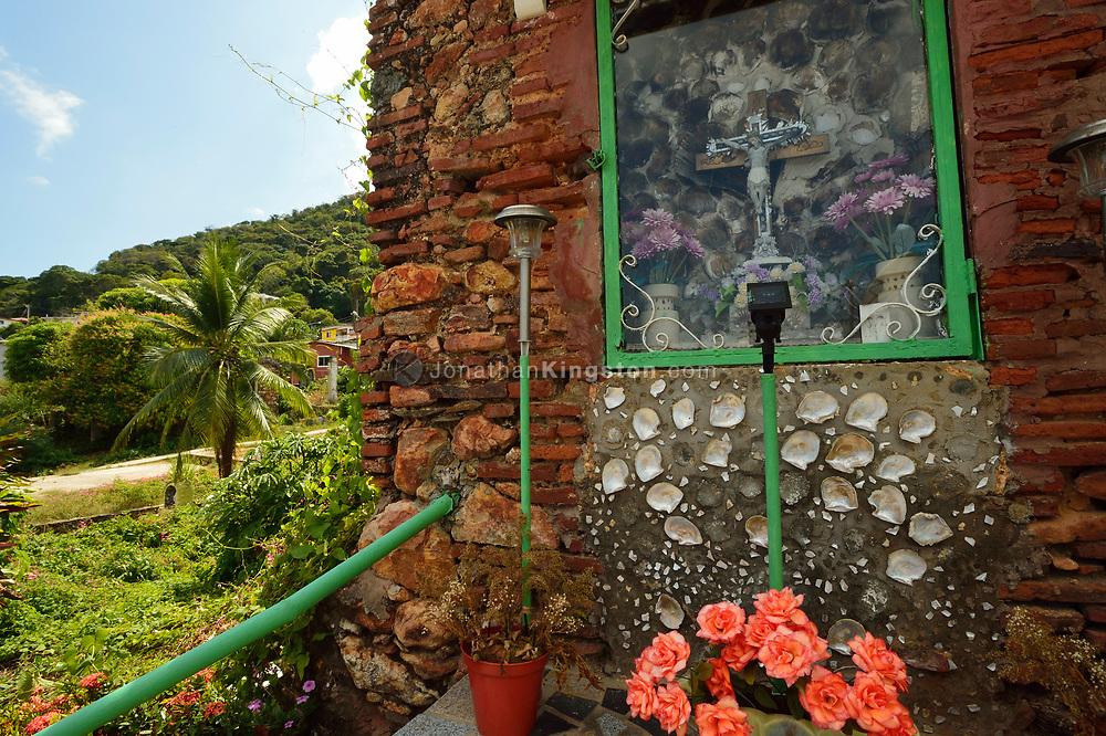 A small shrine with a crucifix behind glass near the San Pedro church, on Taboga Island, near Panama City, Panama.