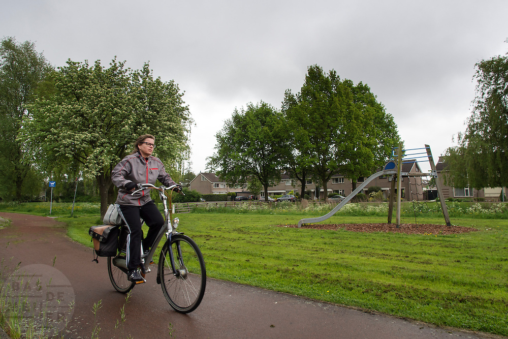 Een vrouw fietst door een parkje in Zevenaar, een plaats in de streek De Liemers in het oosten van Nederland.<br /> <br /> A woman cycling through a park in Zevenaar, a place in the region's Liemers in the east of the Netherlands.