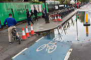 A cyclist rides on the pavement while a section of the CS2 cycling superhighway is blocked due to recent rainfall, on 29th August 2018, in London, England. The CS2 cycle route is about 4.3 miles (6.8 kilometres), from Stratford to Aldgate.