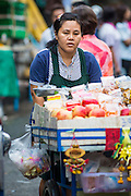 09 OCTOBER 2012 - BANGKOK, THAILAND:  A snack vendor pushes her cart in front of the Bangkok Flower Market. The Bangkok Flower Market (Pak Klong Talad) is the biggest wholesale and retail fresh flower market in Bangkok. It is also one of the largest fresh fruit and produce markets in the city. The market is located in the old part of the city, south of Wat Po (Temple of the Reclining Buddha) and the Grand Palace.    PHOTO BY JACK KURTZ