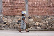 A Zapotec woman walks carrying a basket on her head in the village of Teotitlan de Valle in the Oaxaca Valley, Mexico.