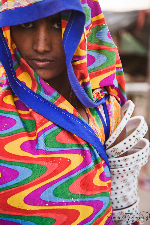 A portrait of a tribal girl peeking out from behind her sari, Phalodi, Rajasthan, India
