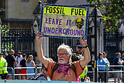 People hold placards and banners as they attend a protest for Climate Change during a two-week protest campaign in central London on Wednesday, Aug 25, 2021.  XR's protest campaign enters its 3rd day of activities putting at a halt the parts of important junctions in Britain's capital. XR launched a two-week protest campaign in London on Monday to demand that the government take greater action to address climate change. (VX Photo/ Vudi Xhymshiti)