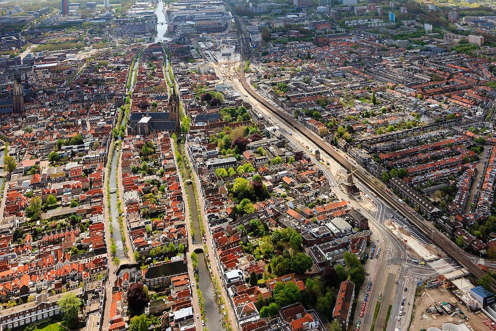 Nederland, Zuid-Holland, Delft, 09-05-2013; Spoorzone Delft, Noordelijke ingang van de spoortunnel, gezien naar het station en verder naar het zuiden. Bagijnetoren en Molen De Roos aan de Phoenixstraat staan nog overeind. Vrnl het water van de grachten Verwersdijk, Voorstraat en Oude Delft..Omdat het bestaande spoorviaduct met slechts twee sporen een flessenhals vorm wordt dit vervangen door een spoortunnel. Verder komt er een ondergronds station, onder het nieuwe stadskantoor..Spoorzone Delft. Because the existing railway viaduct - through the historical inner city - has only two tracks it is a bottleneck. A new underground railway tunnel is being build, it will include an underground station, under the new city hall..luchtfoto (toeslag op standard tarieven).aerial photo (additional fee required).copyright foto/photo Siebe Swart