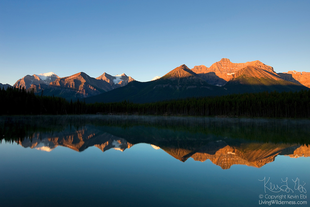 The Bow Mountain Range, part of the Canadian Rockies, is reflected in the still waters of Herbert Lake in Banff National Park, Alberta, Canada.