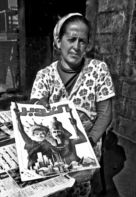 Magazine seller offers a copy of the magazine for sale at her street kiosk.  Vertical image.