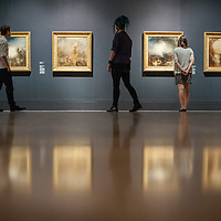 London, UK - 8 September 2014: gallery assistants looks up at paintings from the 1840s<br />  by J.M.W. Turner, during the press preview of The EY Exhibition: Late Turner – Painting Set Free exhibition at Tate Britain