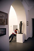 An attendant falls asleep in the Museum of contemporary art in The Castel Nuovo, Naples, Italy. First erected in 1279, it is one of the main architectural landmarks of the city.