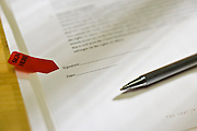 Documents requiring signature and pen on a desk.