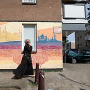 """Nederland Den Haag 31 augustus 2008 2080831 Foto: David Rozing..Bellende moslima loopt voor indiase muurschildering in achterstandswijk Schilderswijk langs. In de wijk zijn verschillende muurschilderingen aangebracht om het multiculturele karakter van de schilderswijk weer te geven. Per muur is een beeld gecreerd uit een cultuur: Indiaas, Afrikaans, Nederlands, Surinaams, Antilliaans en Arabisch.  Doel van de muurschildering: """" Om graffiteurs en onroerend goed eigenaren op een kunstzinnige wijze met elkaar te laten samenwerken en onder afspraak dat de graffiteur ophoudt met illigaal taggen. De graffiteur wordt betaald en krijgt de opdracht om deze muurschilderingen aan te brengen. Meer info: Yolande Weerdenburg 06 24613835.De schilderwijk is een van de 40 wijken van Vogelaar. Deze lijst van 40 Nederlandse probleemwijken is op 22 maart 2007 door Minister Ella Vogelaar van Wonen, Wijken en Integratie bekend gemaakt. De minister duidde deze wijken aan met prachtwijken. In deze wijken zullen gedurende de kabinetsperiode Balkenende IV extra investeringen worden gedaan gezien stapeling van sociale, fysieke en economische problemen die zich daar voordoen..De wijk is in de tweede helft van de 19e eeuw gebouwd. Het is een van de armste wijken in Nederland. Zo'n 87% van de 33.123 geregistreerde bewoners is van niet-Westerse afkomst -- met name Turks, Surinaams en Marokkaans..De Schilderswijk is rijk aan verschillende culturen die boven en naast elkaar leven. Er is veel keuze in voedselaanbod in cafés, kleine restaurants, bars en supermarkten. Er is de Haagsche markt en er zijn winkels waarin verschillende culturen hun deur openen om iets nieuws te verkopen, zoals sieraden- en kledingwinkels. Allerlei stedelijke activiteiten liggen op loopafstand van de Schilderswijk. De Haagse binnenstad ligt 5 minuten lopen vanaf de rand van de Schilderswijk. Tram en ander openbaar vervoer zijn te bereiken op 5 tot 10 minuten loopafstand...Foto David Rozing"""
