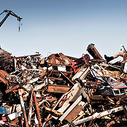 A scrap yard worker enjoying the sunshine whilst taking a break on a large pile of metal scrap.