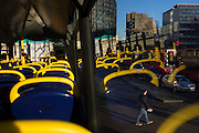 Pedestrians cross a road in Southwark with yellow seating handles from the top deck of a London double-decker bus.