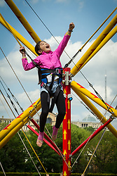 Girl on bungee trampoline, London. Alexandra Palace in the background