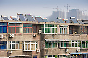 Solar panels and air conditioning on apartments next to the City Wall, Xian, China