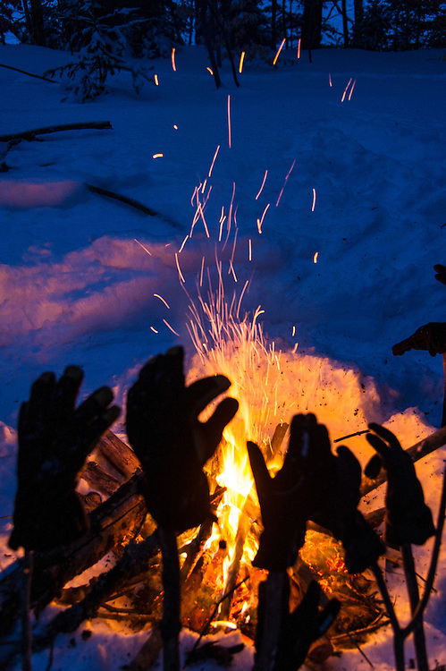 Drying gloves around a campfire while winter camping