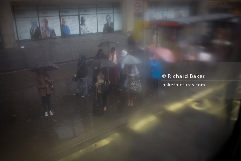 Seen through upper-deck window condensation, a crowd of waiting passengers use umbrellas at a bus stop during damp, gloomy weather in central London.