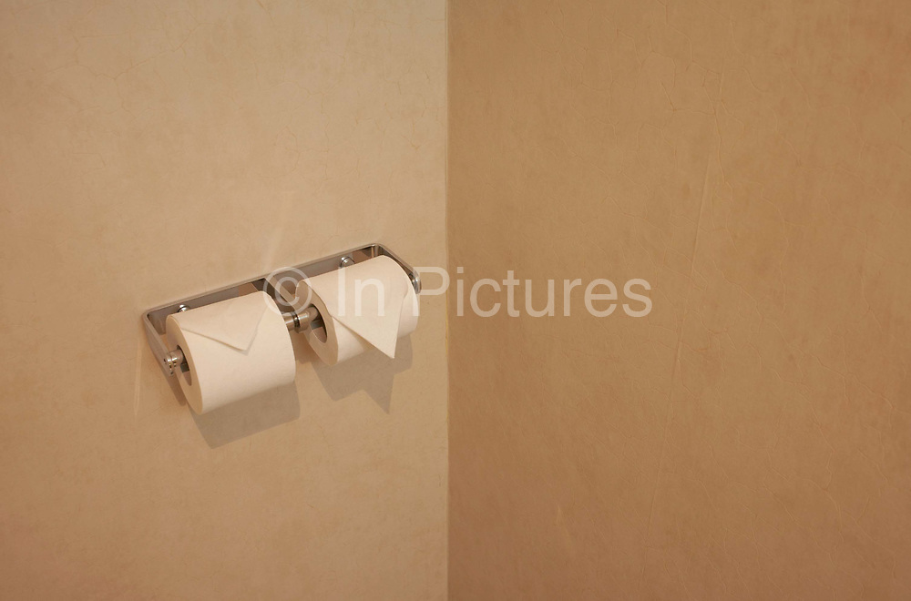Two toilet rolls are ready for use in a Paris hotel room toilet. Folded into triangular, pointed ends that point down to the bathroom floor in a famliar manner known to businessmen and and tourists during overnight stays in these anonymous and generic rest-stops frequented by travellers. Mounted onto a brown wall, the twin toilet roll holders are fixed side by side and have a shiny chrome finish.