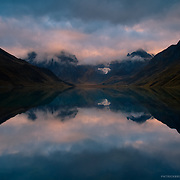 A relfection during sunrise over Lake Carhuacocha in the Cordillera Huayhuash of the Andes Mountains in Peru.