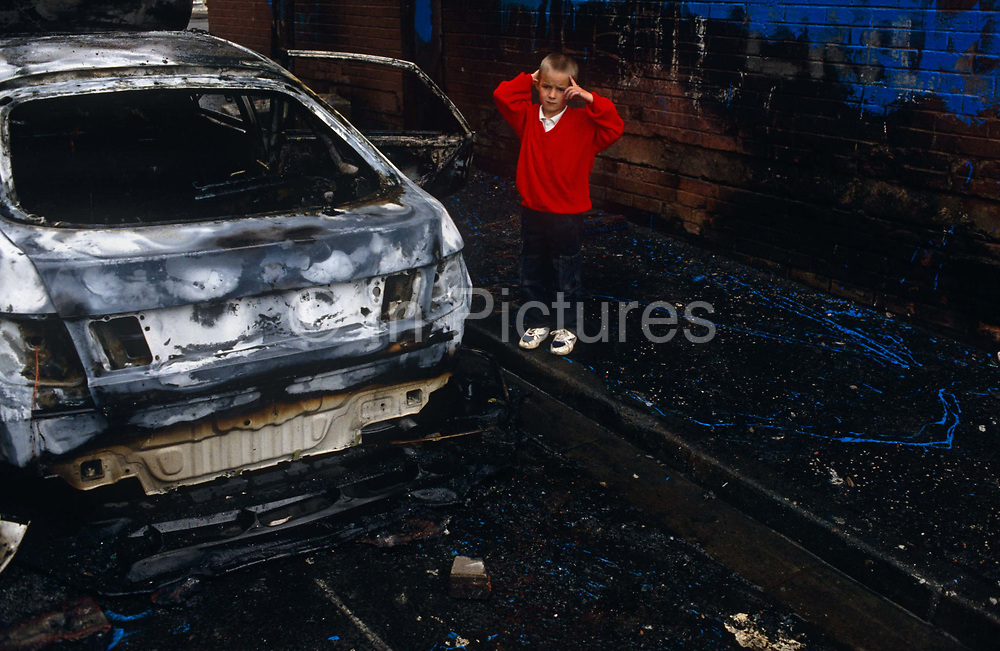 A young boy wearing his school uniform looks traumatised standing next to a burned-out shell of a saloon car that was set alight by vandals beneath the infamous Divis flats of the Catholic Lower Falls Road, West Belfast. He wears a red jumper which contrasts the blue graffiti paint on the wall behind him and the charred ground at his feet. He is alone, a young boy experiencing childhood through the traumas of a violent world Divis Tower was a flashpoint area during the height of the Troubles. 9 year-old Patrick Rooney a child of a similar age to this lad, was the first child killed in the Troubles, was killed in the tower during the Northern Ireland riots of August 1969,
