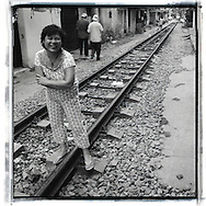 Black and white portrait of a Vietnamese women laughing while standing nearby the railway of Hanoi, Vietnam, Southeast Asia