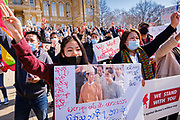 "06 MARCH 2021 - DES MOINES, IOWA: A member of the Burmese community in Iowa makes the three finger ""Hunger Games"" salute during a protest against the military coup in Myanmar. The so called ""Hunger Games salute,"" from the movie ""The Hunger Games"" is used by Burmese to protest the coup. About 300 members of the Burmese community in Iowa gathered at the State Capitol in Des Moines Saturday to protest against the military coup that deposed the popularly elected government of Aung San Suu Kyi and continuing military oppression in Myanmar. There are about 10,000 people in Iowa's Burmese community.        PHOTO BY JACK KURTZ"