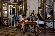 Three Asian girls plan their tour of Venice inside the covered Procuratie Nuovo in Piazza San Marco, Venice, Italy. The Procuratie are three connected buildings on St Mark's Square in Venice. They are historic buildings over arcades, the last of them completed, to finish off the square, under Napoleon's occupation. Venice attracts 22-million visitors each year (for a city of only about 60,000 residents) while the cultural protection organisation, Italian Nostra, warns that Venice can only accommodate about 33,000 visitors per day but currently at least 60,000 daily.