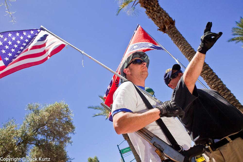 May 29 - PHOENIX, AZ: Self described white supremacists and supporters of Arizona SB1070 with American and Confederate flags protest against a pro-immigrant rally in Phoenix Saturday. They were two of about five people who demonstrated in favor the bill while more than 30,000 people, supporters of immigrants' rights and opposed to Arizona SB1070, marched through central Phoenix to the Arizona State Capitol Saturday. SB1070 makes it an Arizona state crime to be in the US illegally and requires that immigrants carry papers with them at all times and present to law enforcement when asked to. Critics of the law say it will lead to racial profiling, harassment of Hispanics and usurps the federal role in immigration enforcement. Supporters of the law say it merely brings Arizona law into line with existing federal laws.  Photo by Jack Kurtz