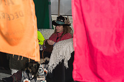 A woman sits on a sofa knitting in a tent erected on the street as hundreds of environmental protesters from Extinction Rebellion occupy Oxford Circus, a pink yacht being the focal point of their presence, with traffic denied access to two of London's busiest streets. London, April 16 2019.