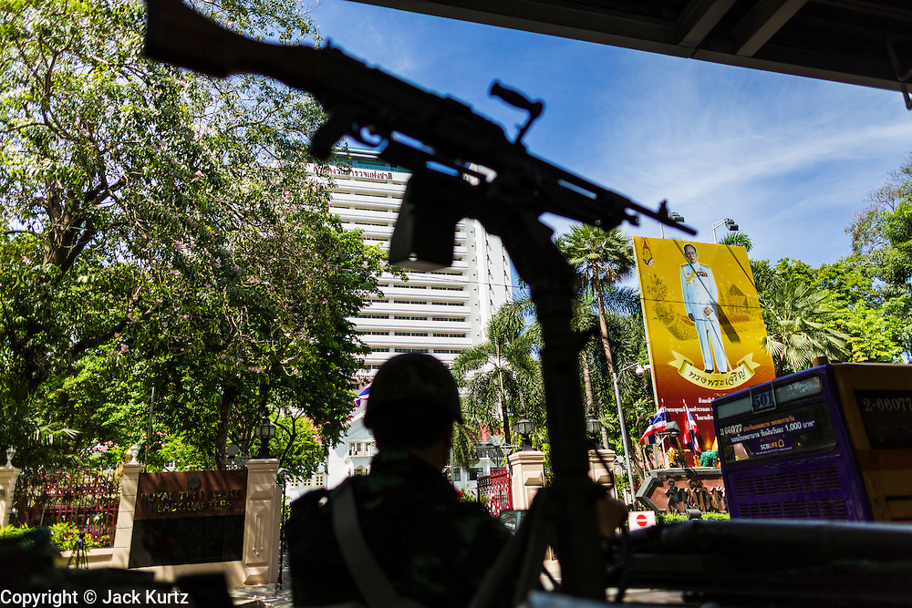 """20 MAY 2104 - BANGKOK, THAILAND:  A Thai army checkpoint in front of a portrait of Bhumibol Adulyadej, the King of Thailand, at the National Police headquarters on Rama I Road in Bangkok. The army has taken over public security functions from the police and ordered many of the police units to stand down. The Thai Army declared martial law throughout Thailand in response to growing political tensions between anti-government protests led by Suthep Thaugsuban and pro-government protests led by the """"Red Shirts"""" who support ousted Prime Minister Yingluck Shinawatra. Despite the declaration of martial law, daily life went on in Bangkok in a normal fashion. There were small isolated protests against martial law, which some Thais called a coup, but there was no violence.  PHOTO BY JACK KURTZ"""