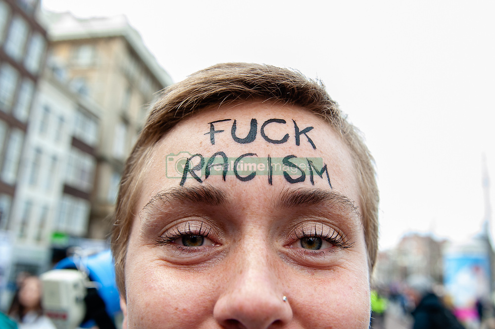 March 23, 2019 - Amsterdam, North Holland, Netherlands - A woman is seen with Fuck Racism written on her forehead during the demonstration..Thousands of people gathered at the Dam square in the center of Amsterdam to demonstrate against racism and discrimination. They ask for diversity and solidarity, against all forms of racism and discrimination. Also, against the two political far-right parties in The Netherlands, the PVV and the FvD which have increased their power during the last elections in the country. A small far-right group showed up during the walk holding two big placards and shouting at the demonstrators. (Credit Image: © Ana Fernandez/SOPA Images via ZUMA Wire)