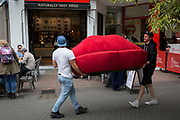 Two workmen carry a red sofa, in the shape of a pair of red lips, on 10th August 2017, in London, England.