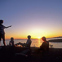 A family enjoys an evening campfire by Lake of The Woods, Ontario, Canada.