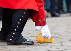 © Licensed to London News Pictures. 05/03/2019. Lichfield, Staffordshire, UK. The annual Shrove Tuesday pancake race taking place in Bore Street in the City Centre of Lichfield. Pictured, the town crier Ken Knowles stoops to pick up a dropped pancake. The event features races for men, women, children and those in fancy dress. The runners are supported by the voice of Town Crier Ken Knowles and the overall winner walks away with a brass and wooden Shrove Tuesday trophy. Photo credit: Dave Warren/LNP