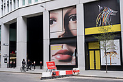 Figures interact with a giant face in the in the City of London financial district, which is still virtually deserted due to the Coronavirus outbreak on 13th April 2021 in London, United Kingdom. The easing of lockdown has begun, with non-essential shops opening, but the financial district remains very quiet.