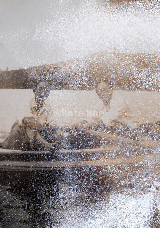 deteriorating vintage photo of friends in rowing boat on the water Japan ca 1950s
