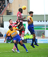 Lincoln City's John Akinde gets above Mansfield Town's Malvind Benning, left and Ryan Sweeney<br /> <br /> Photographer Andrew Vaughan/CameraSport<br /> <br /> The EFL Sky Bet League Two - Lincoln City v Mansfield Town - Saturday 24th November 2018 - Sincil Bank - Lincoln<br /> <br /> World Copyright © 2018 CameraSport. All rights reserved. 43 Linden Ave. Countesthorpe. Leicester. England. LE8 5PG - Tel: +44 (0) 116 277 4147 - admin@camerasport.com - www.camerasport.com