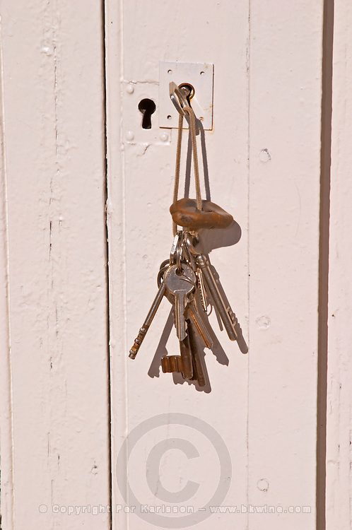The cellar keys, a bunch of keys on a key ring, to the cellar door in the keyhole against a white door - Chateau Haut Bergeron, Sauternes, Bordeaux