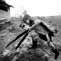 A young boy carrying machetes runs for cover during a rain storm on a small holding farm growing alternative crops. The farm is surrounded by coca plantations. The Government uses ariel fumigation to destroy the coca plants, the chemicals are often carried by the wind or leach through the ground and destroy all crops in the area.<br />