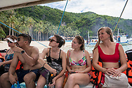Friends from Belgium ride in a traditional bangka boat on a tour of the Bacuit Archipelago around El Nido, Palawan, Philippines. In this picture, the boat is departing Seven Commandos Beach.<br /><br />(July 14, 2019)