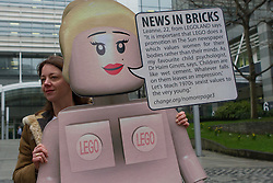 © Licensed to London News Pictures. 26/02/2013. London, UK. Lucy Holmes protests with a spoof female Lego model outside The Sun's News International offices in Wapping, East London on 26 February 2013. Demonstrators are calling for Rupert Murdoch to end topless female models in The Sun newspaper, claiming it is unsuitable for family reading and are using a spoof Lego model, nicknamed 'Leanne' as a campaign tool to target the joint promotion running this week between corporate advertisers, Lego and The Sun which is offering free Lego toys aimed at children. Photo credit : Vickie Flores/LNP