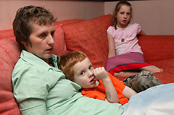 Single parent watching television with her children on the sofa at home,