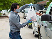 21 MAY 2020 - DES MOINES, IOWA: JOSH MANDELBAUM, a Des Moines City Councilman, hands a bag of meals to people in a drive through emergency food distribution in Evelyn K. Davis Park in central Des Moines. All of the 485 meals were distributed in about an hour. The economic fallout of the pandemic is being felt throughout Iowa. On May 21, 2020, Iowa reported that 187,375 people had filed for unemployment since the beginning of the COVID-19 pandemic and resulting economic shutdown. Emergency food pantry has also increased in that time, as many Iowans in low wage jobs used emergency food banks and pantries for the first time. The Food Bank of Iowa said Thursday that demand in April 2020 was 31% higher than demand in April 2019, mostly because of unemployment caused by the Coronavirus (SARS-CoV-2) pandemic. The emergency food distribution Thursday was organized by the city of Des Moines, Food Bank of Iowa, Central Iowa Shelter and Services, Urban Dreams and Orchestrate Hospitality.       PHOTO BY JACK KURTZ