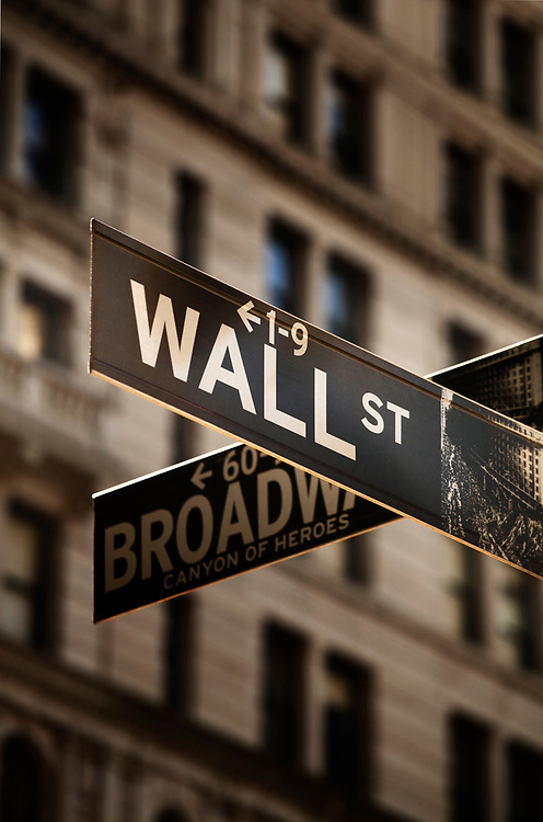 Close up and sepia toned photograph of the Wall Street and Broadway street signs