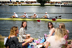 © Licensed to London News Pictures. 04/07/2018. Henley-on-Thames, UK. A group of women lunch on the banks of the Thames River on day one of the Henley Royal Regatta, set on the River Thames by the town of Henley-on-Thames in England. Established in 1839, the five day international rowing event, raced over a course of 2,112 meters (1 mile 550 yards), is considered an important part of the English social season. Photo credit: Ben Cawthra/LNP