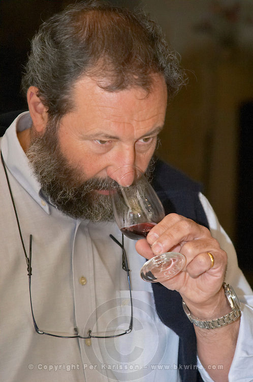 In the wine tasting room, Pascal Delbec, owner and wine maker holding a glass and tasting his wine  Chateau Belair (Bel Air) 1er premier Grand Cru Classe  Saint Emilion  Bordeaux Gironde Aquitaine France
