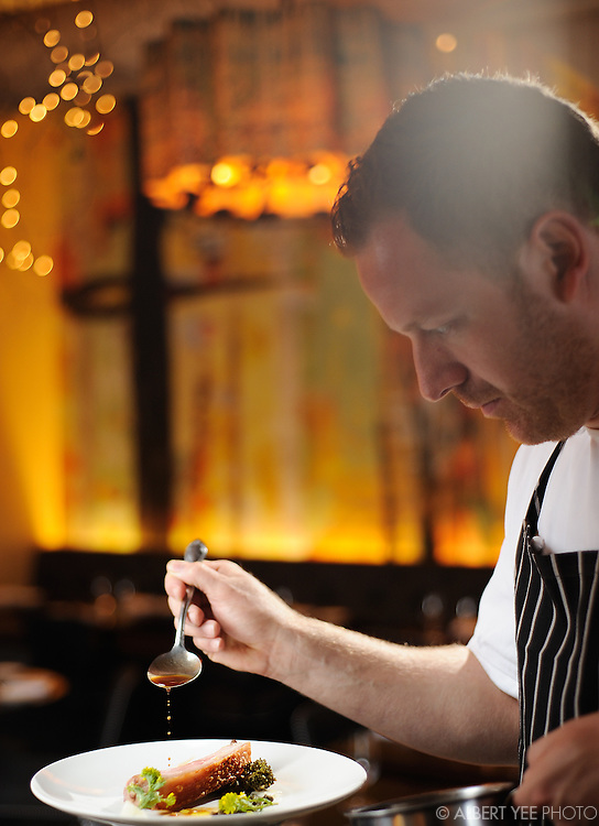 Chef Eli Kulp finishing the pork with broccoli rabe<br /> <br /> Fork Restaurant for Grid Magazine<br /> <br /> March 25, 2014