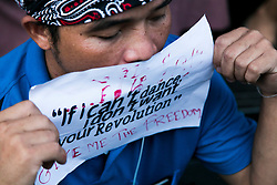 "© Licensed to London News Pictures. 24/05/2014. A protestor covers his mouth with an anti-coup message reading ""if i can't dance i don't want your revolution"" following a Anti-Coup protest in Bangkok Thailand. The Royal Thai army announced a Military coup and have imposed a 10pm curfew.  Photo credit : Asanka Brendon Ratnayake/LNP"